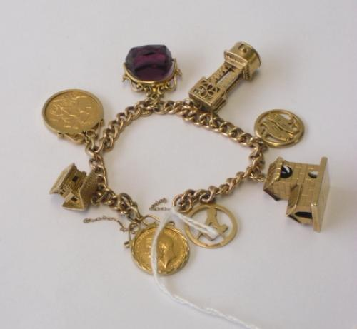 Image of Lot  336  - A 9ct gold charm bracelet having an Edward VII 1906 full sovereign, a George V 1913 half sovereign and six 9ct gold charms including a stone set swivel fob.